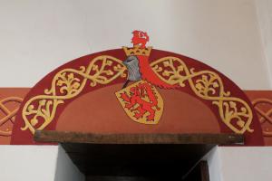 De korfboog boven de deur met wapen van Holland en helmteken